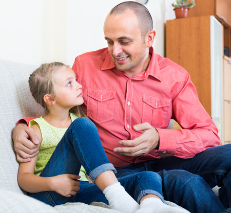 offence: Serious father rebuking small daughter for offence Stock Photo