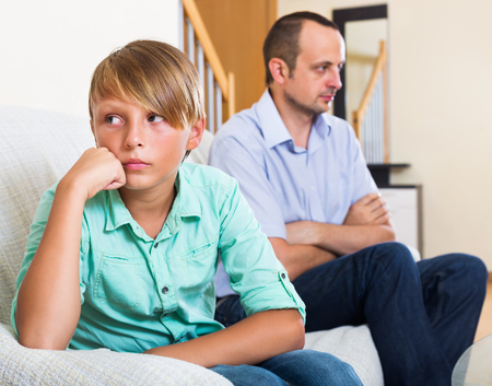 Ordinary father and teenage son in the middle of argue in home Stock Photo