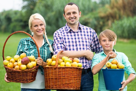 30 to 35: Happy family with teenager holding baskets with apples outdoors