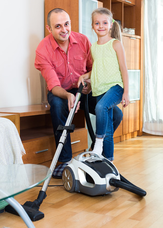 cleanup: girl helping father to do regular clean-up indoors