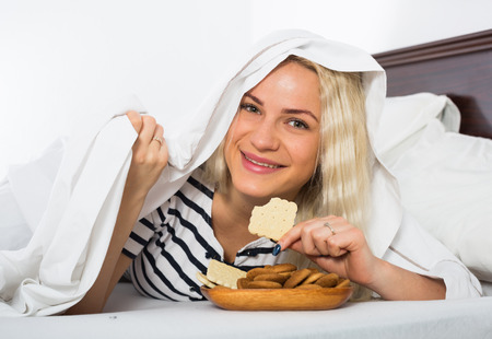 25 35: Young woman eating biscuits hiding under sheet in bed