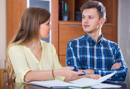25 35: Young couple filling documents for insurance sitting at the table at home