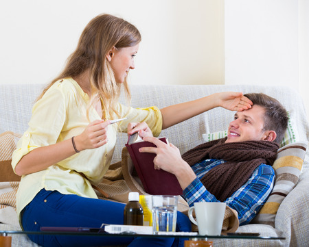 Loving wife taking care of young sick husband lying on sofa at home Stock Photo
