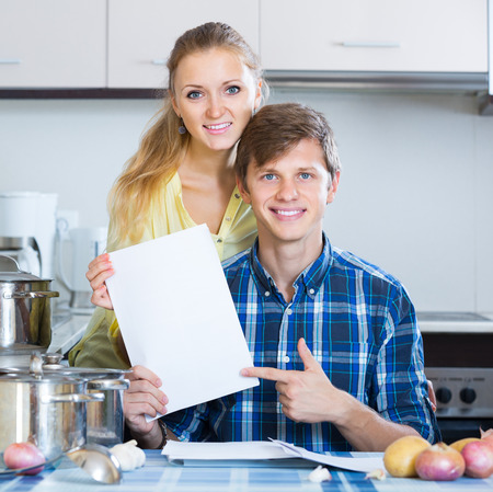 middle joint: positive american spouses signing documents and smiling at kitchen