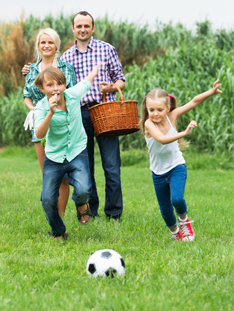 socker: Positive active children and parents running with ball at sunny day