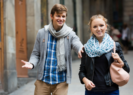 sidewalk talk: Nice-looking male student chasing pleased girl at the outdoor date