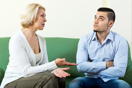 adult intercourse: Young man and his elderly girlfriend having serious conversation indoors Stock Photo