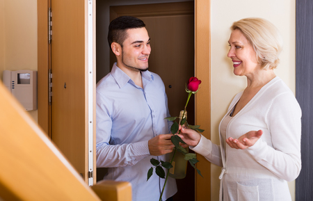 mismatch: Mature woman meeting smiling young boyfriend with flowers and wine in hands