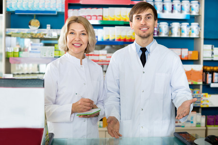 farmacy: Portrait of two cheerful smiling pharmacists working in modern farmacy Stock Photo