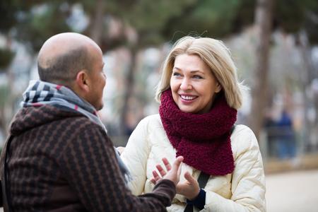 55 60: Portrait of positive mature couple having interesting conversation outdoors Stock Photo