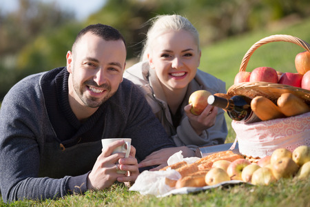 sandwitch: Portrait of happy young spouses lounging in sunny spring day at picnic outdoors