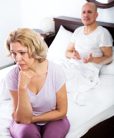 impotent: Senior man and unhappy woman getting through scandals and blamings in bedroom