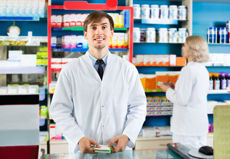 farmacy: Portrait of two friendly charming pharmacists working in modern farmacy