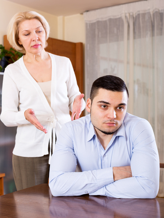 gigolo: Attractive guy and his mature girlfriend having serious conversation indoors. Focus on the man Stock Photo