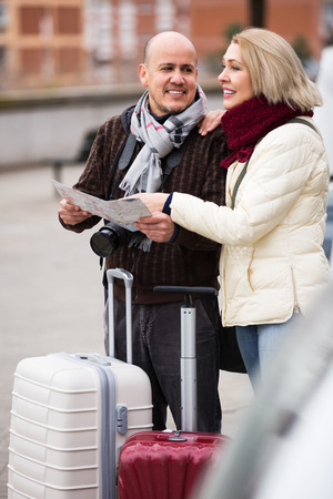 a two wheeled vehicle: Elderly happy spouses with baggage and paper map outdoors
