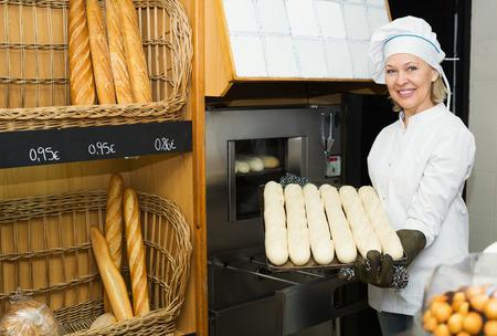 55 60: Portrait of pleasant mature female baking baguettes in bakery Stock Photo