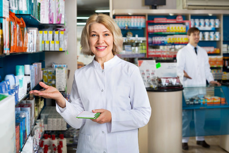 farmacy: Portrait of two  glad smiling pharmacists working in modern farmacy