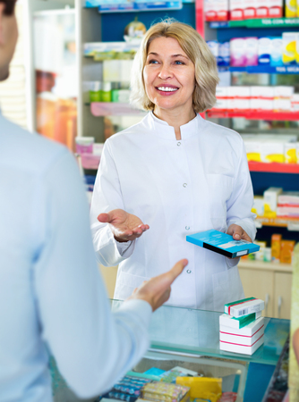farmacy: Female pharmacist counseling customer about drugs usage in modern farmacy