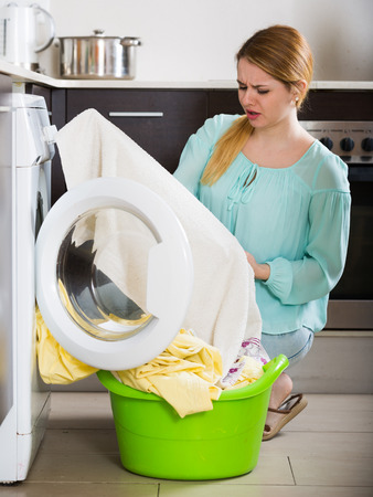 drained: Tired woman with musty linen after lame laundry at home Stock Photo