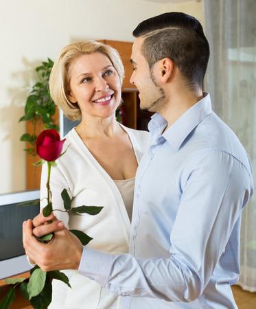 mamá hijo: Hijo adulto americano pidiendo a la madre superior a bailar en casa
