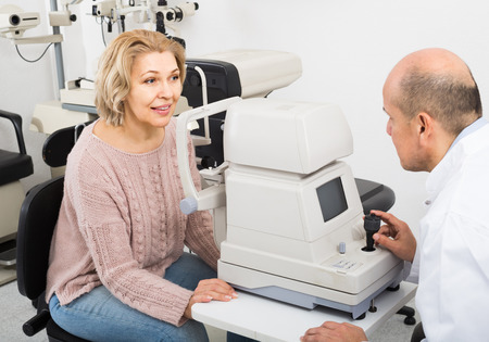 slit: happy mature optician examinating eyesight with aid of slit lamp