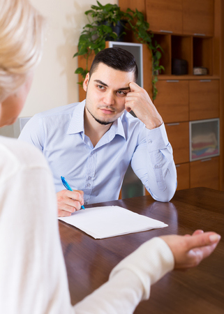 mismatch: Adult son helping senior mother with documents for buying apartment