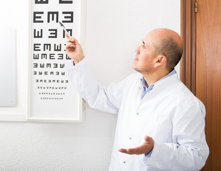 happy nurse: Senior male ophthalmologist pointing at letters of eye chart Stock Photo