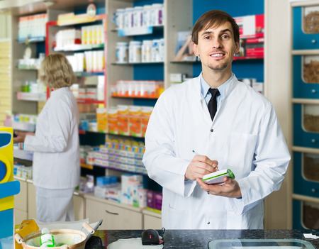 farmacy: Portrait of positive young european male pharmacists working in modern farmacy