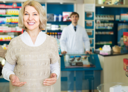 chooses: Portrait of happy american mature woman chooses drugs at the pharmacy Stock Photo