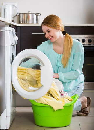 charwoman: Portrait of satisfied housewife with bed linen near washer