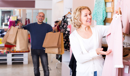 55 60: Cheerful man with bags waiting for mature woman selecting dress in boutique