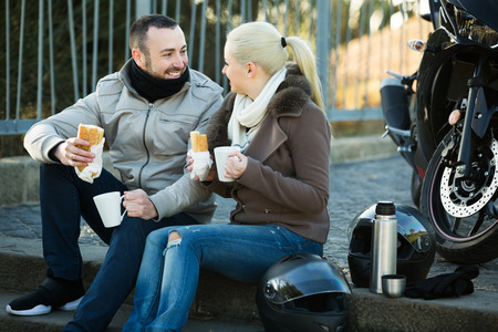 sandwitch: Young smiling adults drinking coffee and chatting near motorcycle