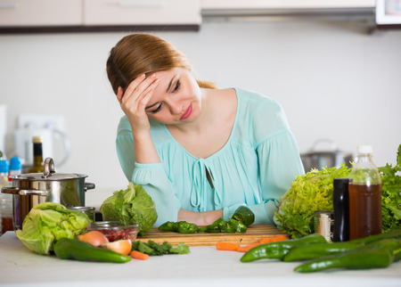 unwillingness: Female tired of vegetarian meal standing at kitchen table
