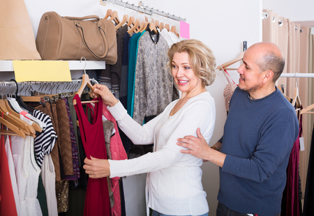 spouses: Happy elderly spouses choosing new dress and smiling in boutique