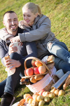 sandwitch: Smiling young spouses lounging in sunny spring day at picnic outdoors