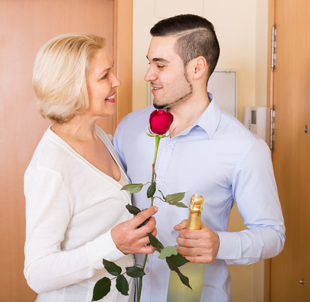 mismatch: Smiling elderly woman meeting young handsome boyfriend with flowers and wine in hands at doorway