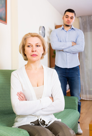 strife: Conflict between adult son and aged mother at home Stock Photo
