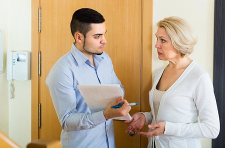 rapacity: Collector is trying to get the debts from mature housewife Stock Photo