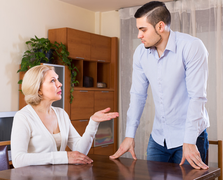 Aged female and young boyfriend discussing something with serious faces at home Stock Photo