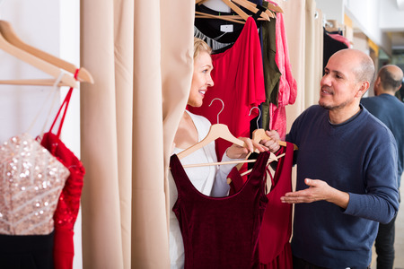 fitting in: Portrait of smiling mature couple trying on new wear in fitting room at boutique Stock Photo