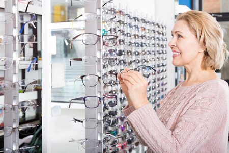 55 60: Senior woman trying spectacles frames and smiling near a stand Stock Photo