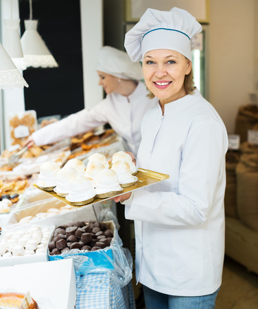 50 60: Elderly seller and assistant at confectionery display with pastry Stock Photo
