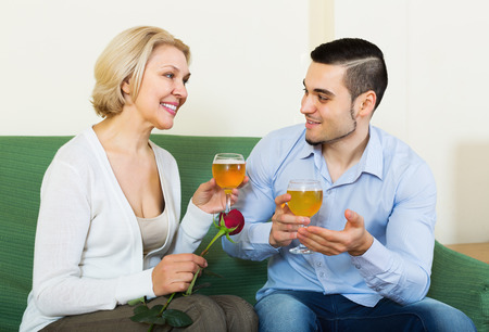 mismatch: Happy elderly woman chatting with young boyfriend indoors Stock Photo