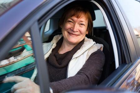 75s: Portrait of female senior driver smiling in car