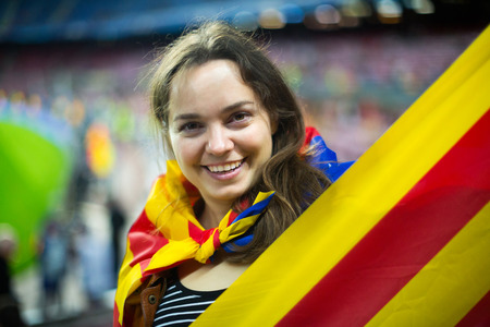 rooting: Excited positive girl with Catalonia flag rooting for football team