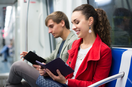 30 to 35: Young passengers in metro wagon reading with electronic books