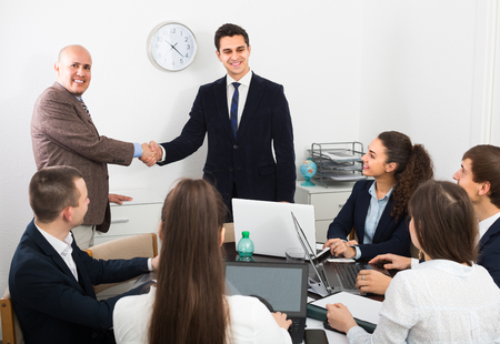 co operation: Two professional managers shaking hands at business meeting