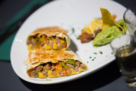 tex mex: Mexican burrito with meat and beans filling served with guacamole