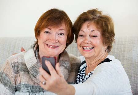 65 70: Modern mature women using mobile phone for image together Stock Photo