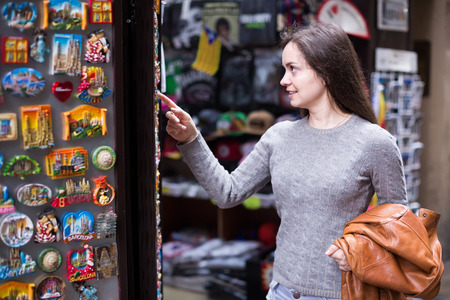 Positive young woman choosing things for memory in souvenir shop Stock Photo
